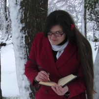 Halo in red coat and snowy landscape, writing in a leatherbound journal, grinning at the camera