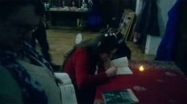 Halo Quin, with pixie ears and knitted wings, signing a copy of her book by candlelight.