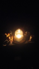 An altar lit by a bright lantern-candle in the dark, outside, with apples and drinking cup barely visible.
