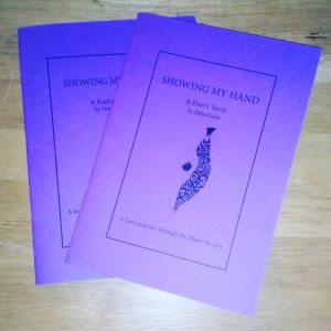 "Two violet booklets with a butterfly emerging from a crysalis depicted on the cover, on a wooden surface. Title: ""Showing My Hand: a Poet's Tarot, by Halo Quin""."