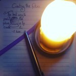 "A birds-eye view of a lit, large cream candle, lighting a stainless steel pen and a journal page with a quote ""the best way to predict the future is to create it."" and a purple ribbon bookmark."