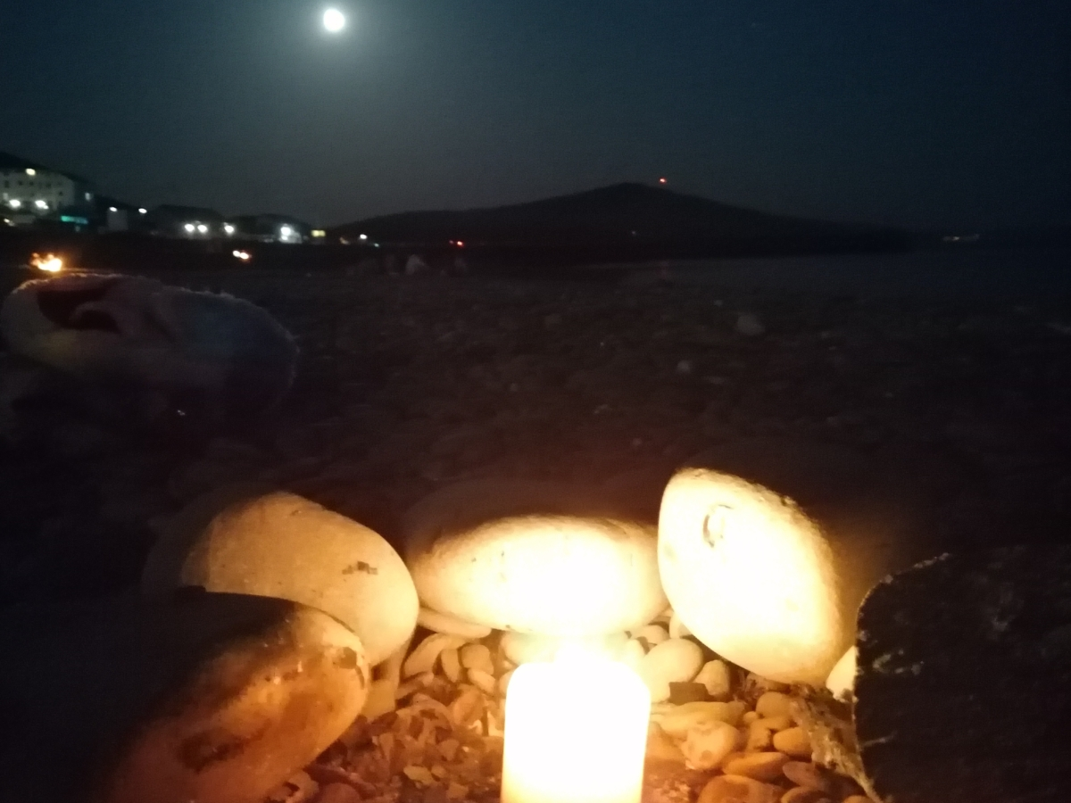 a lit candle in a stone fire circle on a dark beach, full moon in the distance